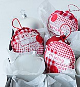 Hand-sewn patchwork Christmas tree decorations made from various red and white patterned fabrics