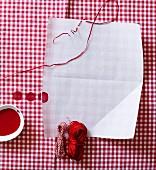 Weißes Blatt Papier auf rot-weiß kariertem Stoff mit verschiedenen Garnrollen und roter Farbe