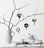 Vintage family photos in pastry cutters and bells hung from branches in china jug