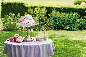 Romantic, festive cake on elegant cake stand and silver basket decorated with roses in summer garden