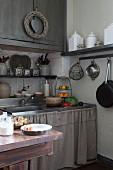 Many shelves of vintage storage jars and linen curtain on sink base unit in Mediterranean kitchen