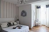 Schlafzimmer im französischen Stil in Grau und Weiß mit gestreifter Tapete und einem barocken Stuhl