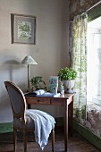 Small wooden desk and Baroque chair next to window with green toile de jouy curtains