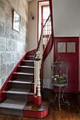 Treppenhaus eines französischen Landhauses aus dem 18. Jahrhundert in Rot und Grau mit einer Steinwand und nostalgischer Vogelvoliere