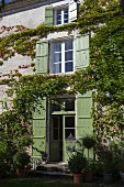 Façade of 18th-century, French country house covered with Virginia creeper and with green window shutters