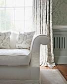 Ecke eines klassischen Sofas vor Sprossenfenster mit Vorhang und Ornament-Tapete