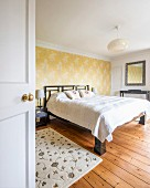 Double bed against accent wall with yellow wallpaper in simple master bedroom with rustic wooden floor seen through open door