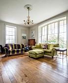 Sofas mit Samtbezug auf Holzdielenboden, seitlich geschwungene Fensterfront in grossräumiger Wohnzimmerecke