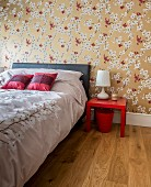 Satin bed linen and floral wallpaper with golden background in elegant bedroom with Oriental ambiance
