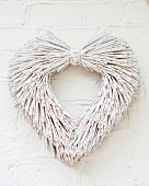 Heart-shaped wreath of whitewashed straw hung on wall