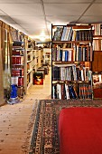 Section of red upholstery on Oriental rug in foreground and bookcase partition in long interior
