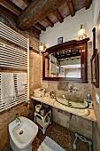 Rustic bathroom with wood-beamed ceiling, washstand with modern glass basin and white, heated towel rail above bidet to one side