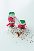 Cress seeds in screw-top jars with pictures of plants on lids tied with ribbons as Easter gift