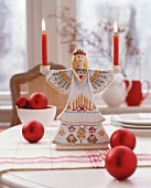 Scandinavian, Saint-Lucy candlestick and red Christmas-tree baubles on table