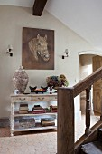 Console table, painting of horse and old wooden staircase in rustic-style hallway