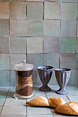 Still-life arrangement of antique drinking cups against kitchen wall with rustic tiles