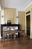 Antique desk in front of open fireplace with marble surround