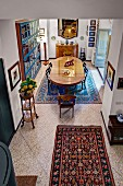 View down from gallery onto patterned rug and stone floor and dining area with antique, oval table in background in traditional interior