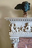 Detail of antique mantelpiece with relief carvings of figures and metal head on plinth