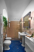 Traditional bathroom with blue tiled floor and shower area with glass screen (Villa Cimbrone Hotel)