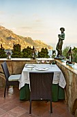 Sculpture on terrace parapet wall, table set for two and coastal landscape in background
