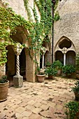 Innenhof der italienischen Villa Cimbrone, mit berankten Arkaden, Pflanzentöpfe auf Terrakottaboden