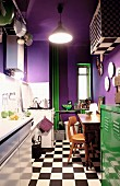 Purple walls, green metal locker and heating pipes in small kitchen with chequered floor