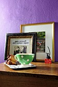 Retro cup on tray in front of framed photos