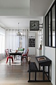 Dining area and decorative station clock above antique school desk in elongated, open-plan interior