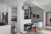 Kitchen area behind partially glazed partition in open-plan interior
