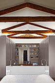 Renovated bedroom with exposed, rustic roof beam structure, bed with headboard, pale grey wardrobes and bookcase