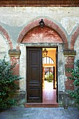 Half-open double doors leading into courtyard of Italian manor house with peeling façade