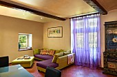 Italian, designer sofa and ottoman in green and purple, terracotta floor tiles and purple, voile curtain