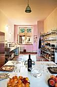 Einfache Loftküche mit offenen Metallregalen und in Marmortechnik farbig abgestufter Wand; gedeckter Tisch im Vordergrund