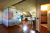 Bed with mosquito-net canopy and America flag in attic room with writing desk under sloping skylights