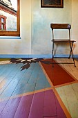 Wooden floor with geometric segments painted in different colours and marbled wall panels