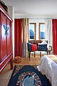Bedroom in shades of red and blue with painted, ethnic cabinet, hand-crafted bench and mixture of curtains in prefabricated house