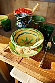 Place setting with painted ceramics and green beakers on rustic wooden table