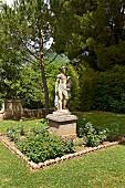 Antike Steinstatue auf Sockel in einer Rabatte, im Park von Villa Cimbrone