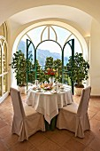 Breakfast table in elegant interior with vaulted ceiling; open arched balcony doors with a view in background (Hotel Villa Cimbrone)