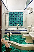 Luxurious bathroom with curved step, green floor tiles, fitted bathtub and blue and green floral wall tiles (Hotel Villa Cimbrone)
