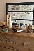 Spindles, vintage stamp and bundle of driftwood on top of chest of drawers with vintage picture frame in background
