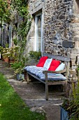 Cushions on wooden garden bench against façade of stone house