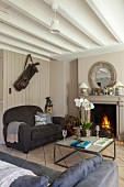 Open fireplace, grey sofas and exposed ceiling beams in living room