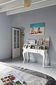 Wooden floor and walls painted in grey and pictures on console table in bedroom