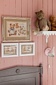 Pictures of teddy bears and soft toys on shelf on pink board wall