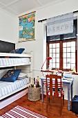 Etagenbett und Stuhl mit Flaggenkissen an lila Schreibtisch vor dem Fenster