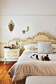 Dog lying on double bed with pretty gilt headboard, Rococo-style bedside cabinet and vintage sconce lamp