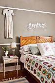 Crocheted patchwork blanket on wooden bed and antique bedside table below white bird motif on grey wall