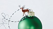 Green Christmas bauble decorated with miniature reindeer figurine